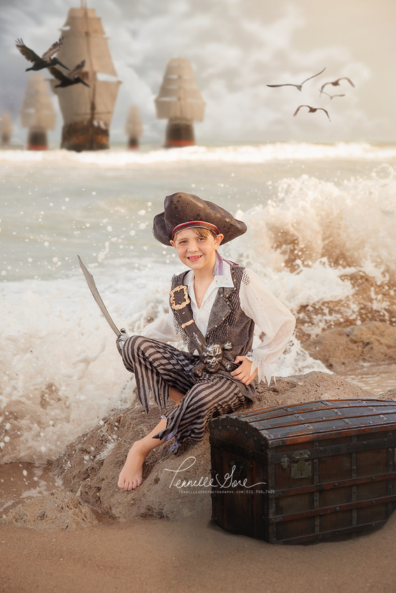 Boy dressed as pirate sitting on a rock, with waves crashing, and pirate ships in the distance.