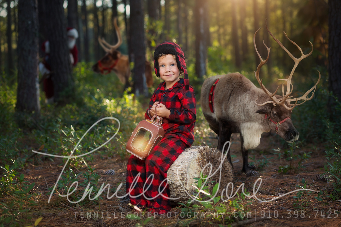 Santa and reindeer meet little boy in pajamas on a wooded trail.