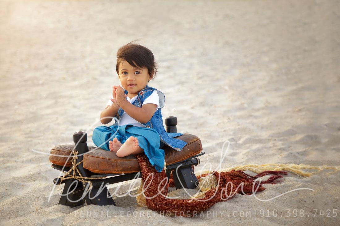 One year old boy on the beach, camel saddle